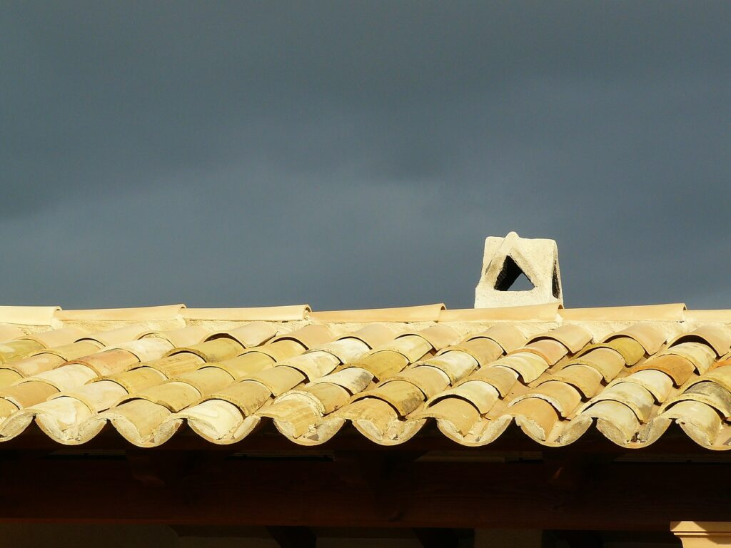 shingled roof with dark sky in background